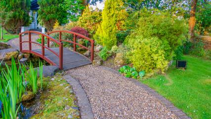 Little wooden arched bridge in garden,