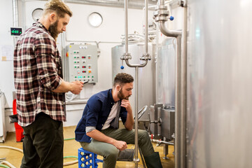 men with tablet pc at craft beer brewery kettle