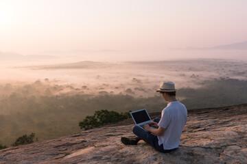 Man and laptop at sunrise
