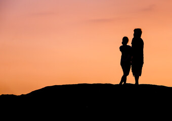 Couple on the beach silhoueete with sunset red sky.
