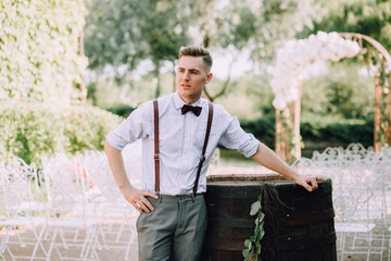 A handsome young male groom in a shirt, bow tie, trousers and suspenders poses next to a barrel for wine