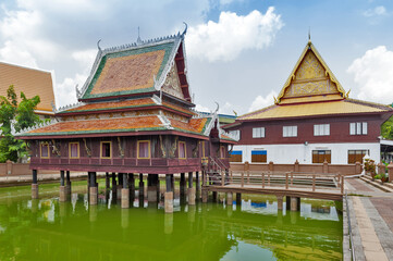 Ho Trai - Traditional Thai-style building used as a library that houses Buddhist scriptures (Tripitaka or Pali Canon) located at Wat Mahathat Temple in downtown Yasothon, Thailand