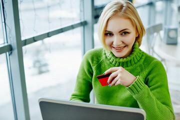 Beautiful girl wearing green sweater in cafe