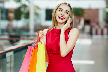 Cute girl with red lips standing with shopping bags