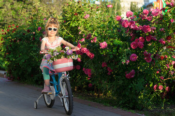 Happy girl rides a bicycle with flowers in a basket.