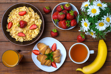 Healthy breakfast: corn flakes, strawberries, juice, tea and croissant.