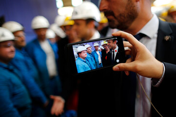 A guest takes a picture with a cellphone of French President Emmanuel Macron who visits the STX Les Chantiers de l'Atlantique shipyard site in Saint-Nazaire