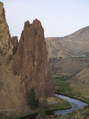 The rugged Smith Rocks and surrounding hills in Central Oregon with a trail at the bottom and the Crooked River winding around on an overcast summer day.