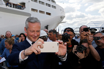 French Economy minister Bruno Le Maire takes a picture of French President Emmanuel Macron near the MSC Meraviglia cruise ship during a visit to the STX Les Chantiers de l'Atlantique shipyard site in Saint-Nazaire