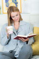 blonde junge frau liest entspannt in einem buch
