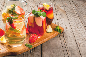 Traditional summer drink sangria - red, pink and white. With champagne, pink and red wine, strawberries, oranges, lemon, green apple and grapefruit. On a wooden rustic table, copy space