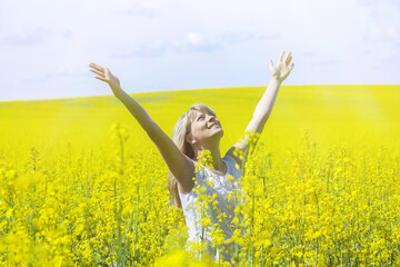 Woman with long hair standing on yellow rapeseed meadow with raised hands. Concept of freedom and happiness.