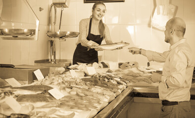 male customer selecting cooled fish in local fishery