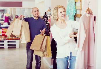 Man with bags waiting for woman selecting dress