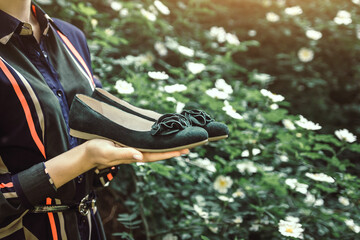 Woman holds a pair of flats
