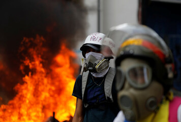 Demonstrators look on as motorcycles belonging to riot security forces are set on fire during a rally against Venezuela's President Nicolas Maduro in Caracas, Venezuela