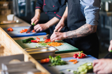 Chef cuts the vegetables into a meal. Preparing dishes. A woman uses a knife and cooks.