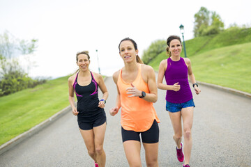 Three relaxed woman runners on a paved jogging daylight