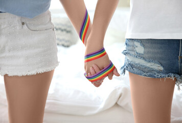 Young lesbian couple holding hands with rainbow ribbon, closeup