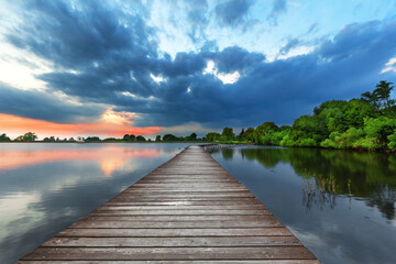 Wooden path bridge over lake at stormy sunset
