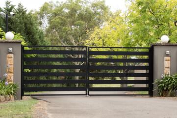 Black metal driveway entrance gates set in brick fence