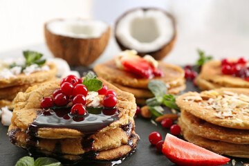 Stacks of delicious coconut pancakes with sweet sauce, berries and mint on slate plate, close up