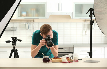 Young man photographing food in photo studio