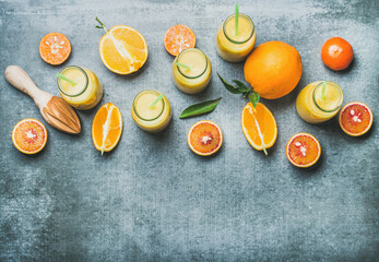 Healthy yellow smoothie with citrus fruit and ginger in bottles over grey concrete background, top...
