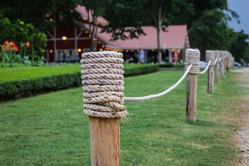 A white rope tied to a wooden fence at a garden.