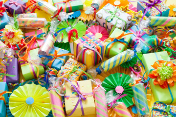Gifts, garland, festive decor and confetti. Yellow background.