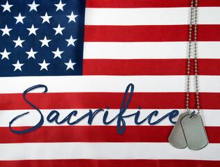 word sacrifice and military dog tags on American flag