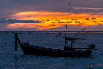 Traditional Thai fishing boat in the evening or morning. Seascape view of Andaman sea from Thailand.
