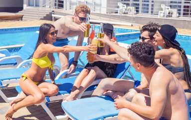 Cheers. Group of cheerful friends drinking cocktails and beer during party at the pool. They clink glasses and smiling
