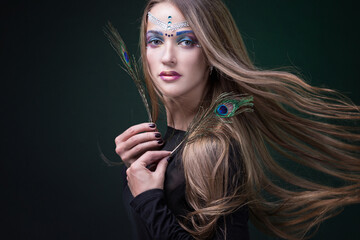 Portrait of a girl, model with peacock feathers in the studio.
