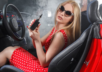 Beautiful sexy woman is sitting in the car and vaping. Red car and red dress. Cloud of vapor.