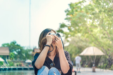 Hipster woman taking photos with retro film camera in outdoor city park,beautiful girl photographed in the old camera