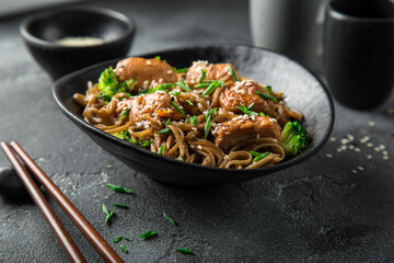 asian soba noodle and teriyaki salmon  in black bowl