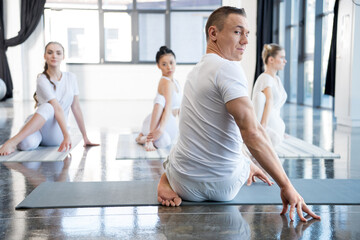 yoga trainer and his group practicing half spinal twist pose in gym