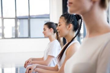 Side view of young women in sportswear meditating at yoga class