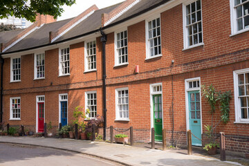 Restored Victorian red brick houses with colored doors on a local road in London, UK