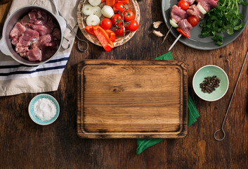 Kitchen board with shish kebab and various vegetables