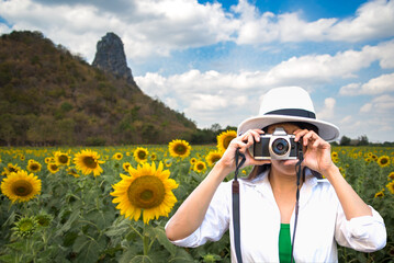 Traveler women covering her face with the camera in the sunflower field, Thailand