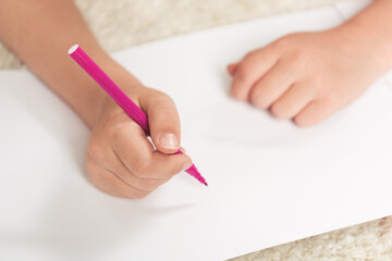 cropped shot of kid drawing with felt pen on blank paper sheet