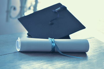 Black mortarboard with blue tassel  and graduation diploma