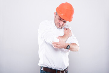 Portrait of contractor wearing hardhat holding elbow like hurting