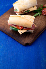 Sandwich with jamon, arugula, tomatoes, cheese on wooden board blue background. Rustic. Two.