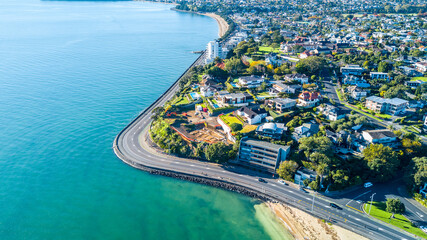 Aerial view on a road running along sea shore with residential suburbs on the background. Auckland, New Zealand.
