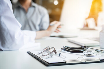 Healthcare and Medical concept, patient listening intently to a female doctor explaining patient symptoms or asking a question as they discuss paperwork together in a consultation