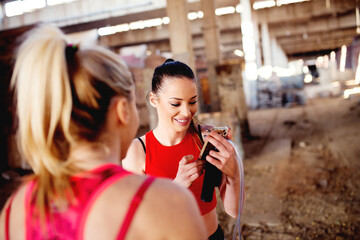 Searching for best soundtrack for training. Music is best motivation for workout. Group of fitness females preparing for training.