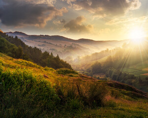 foggy hillside in rural area at sunset